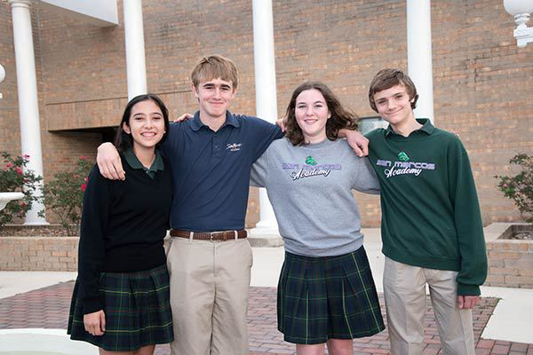Photo of 4 students standing in the courtyard