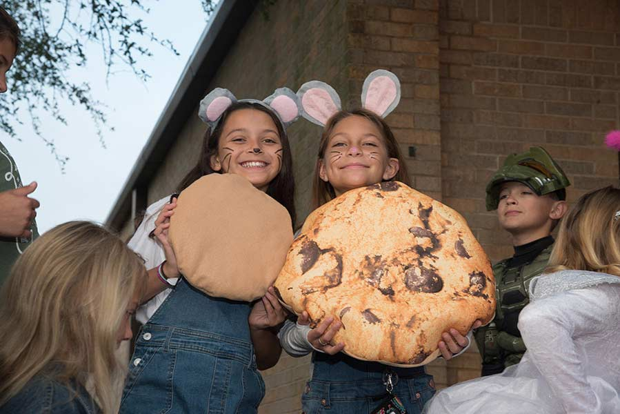 Two students dressed as mice hold giant cookies on costume day.