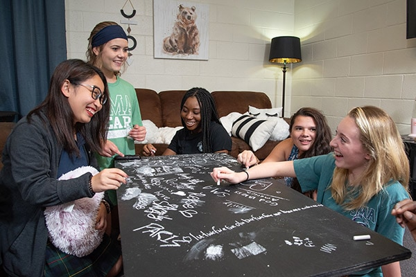 Girls playing games with chalk in a dorm common area