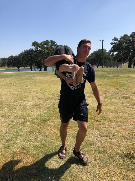One student carries another over his shoulder for a workout