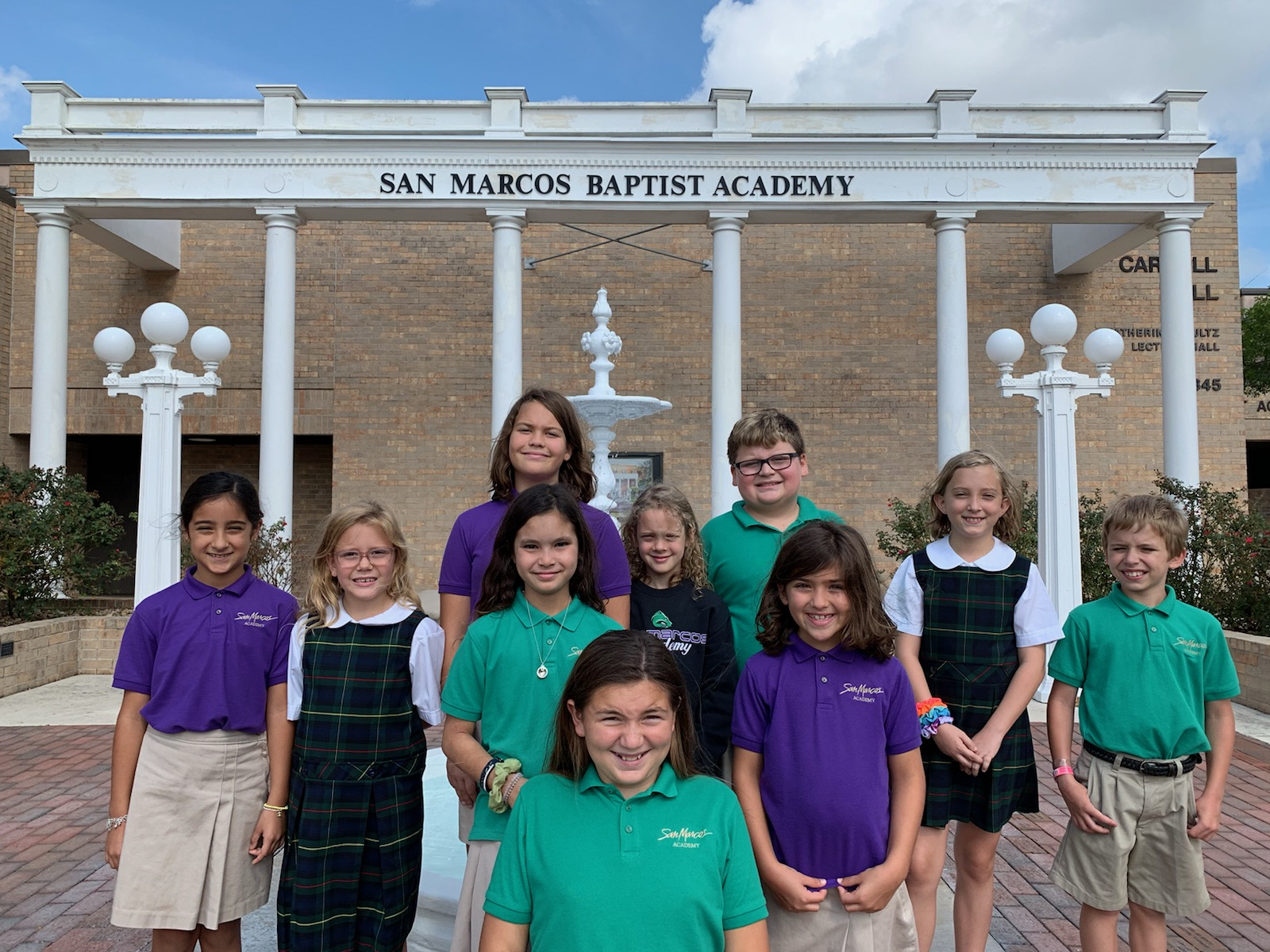 Lower School students posing by the fountain at our boarding school in Texas
