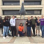 Seniors touring a college campus and posing near a landmark statue