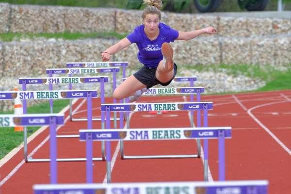 Woman jumping over hurdles