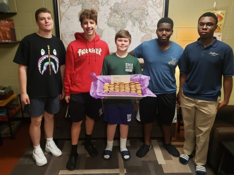 Students holding a tray of fresh-baked cookies