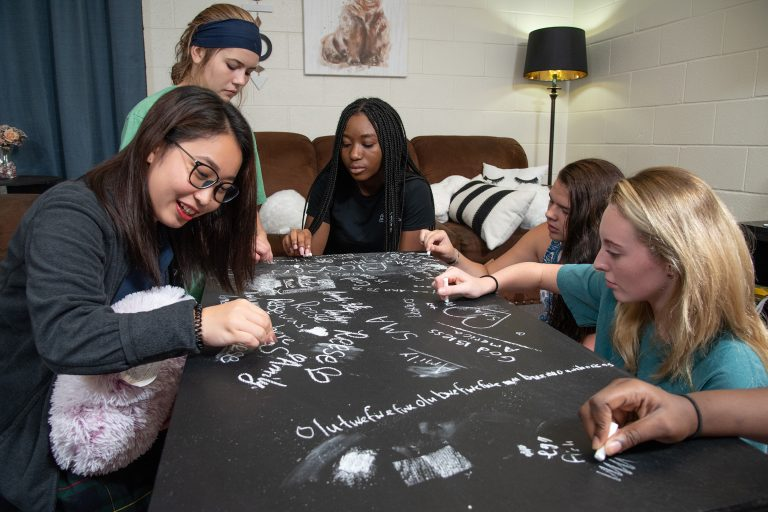 Boarding school students from Houston Texas participating in a group activity in a dorm common area