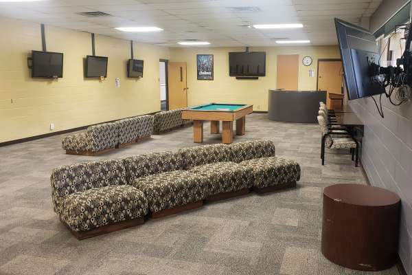 Couches, TVs and a pool table at the rec center game room