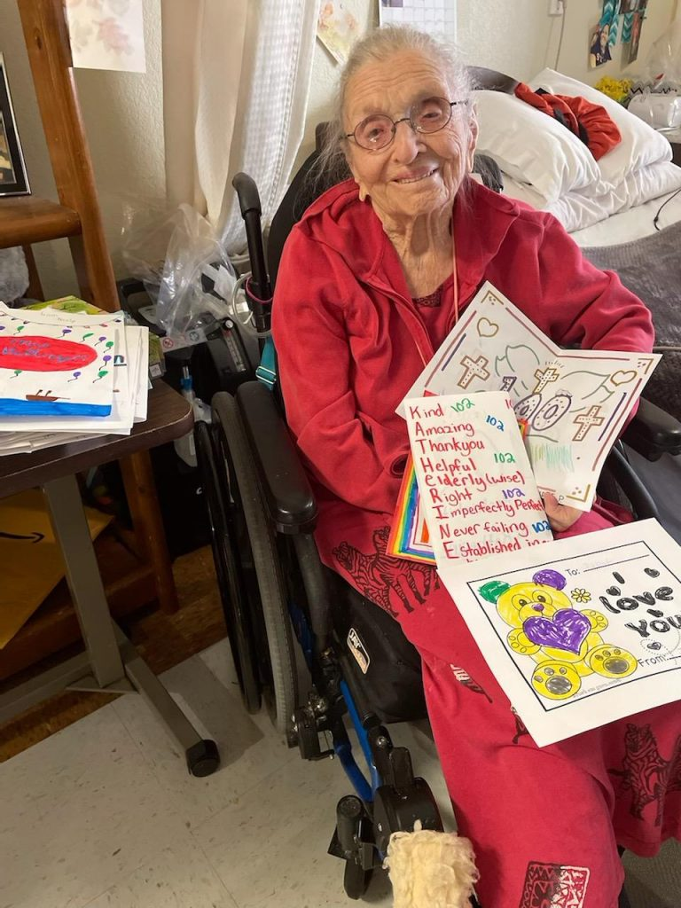 Centenarian with 100th day of school cards